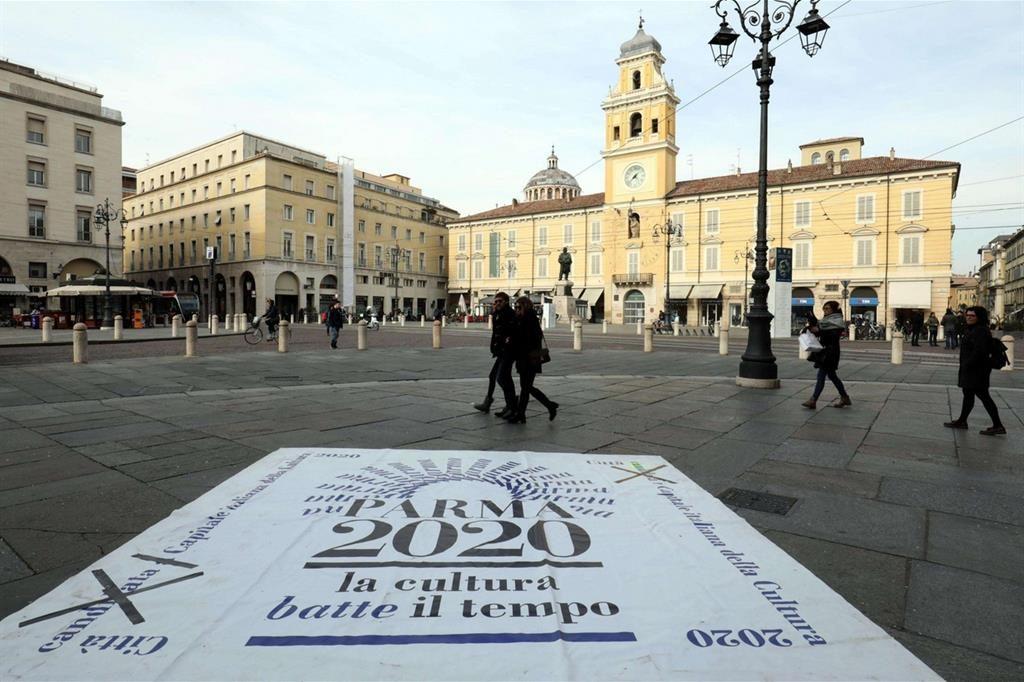 Logo di Parma  su asfalto davanti alla piazza con persone che passano