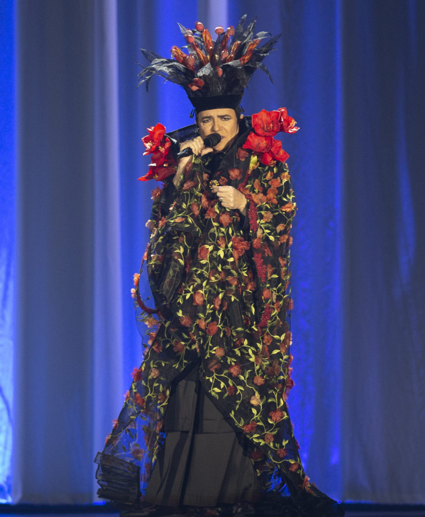 Renato Zero con microfono in mano canta con un vestito lungo colorato con tanti fiori e indossa un cappello vistoso con delle rose