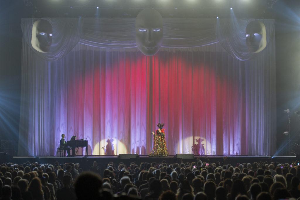 il concerto del tour di Zero il folle comincia con il sipario chiuso. stefano Senesi seduto al piano forte e Renato con un vestito largo a fiori e un cappello vistoso canta