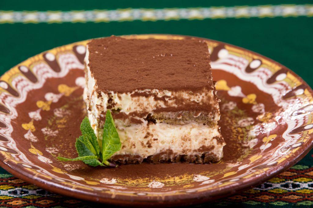 una porzione di tiramisù in un piatto decorato con polvere di cioccolato e una foglia di menta