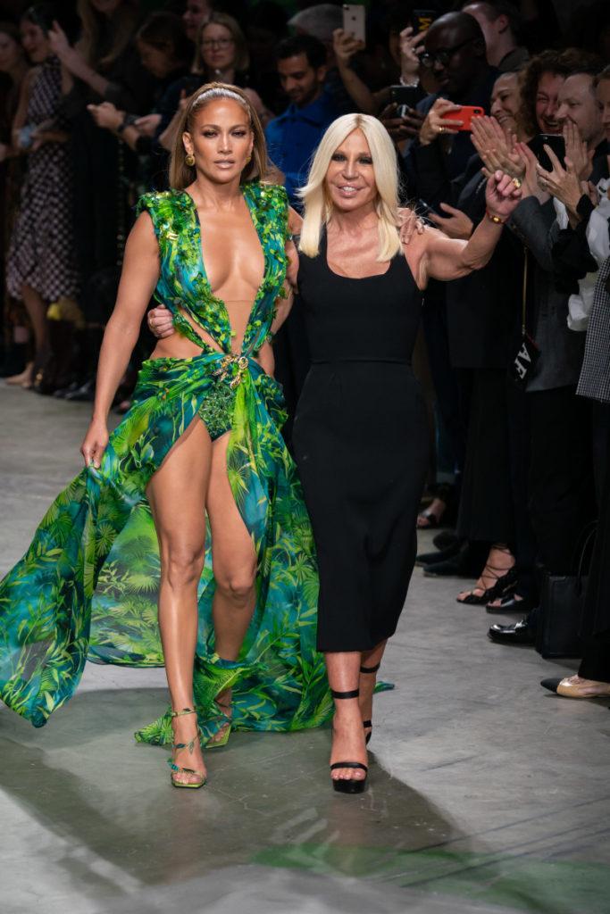 Donatella Versace a braccetto di una modella vestita con un abito scollatissimo verde aperto