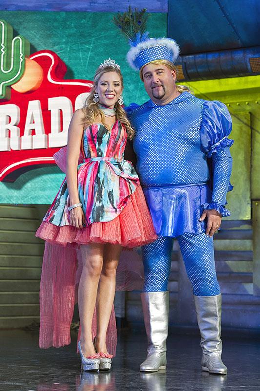 max pieriboni travestito da principe azzurro, accanto a una ragazza bionda che intepreta la principessa, che indossa un vestitino rosa corto fino alle ginocchia, con un velo rosa che scende giù dietro la schiena, sul palco di colorado