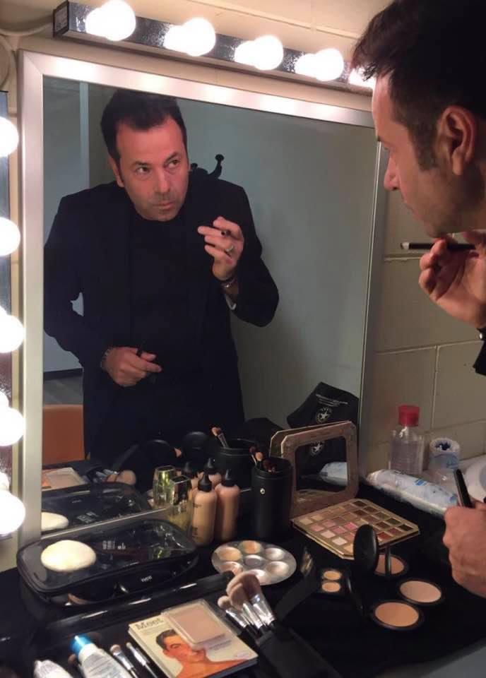 Paolo Demaria truccatore mentre si specchiia in uno specchio con tante lampadine intorno alla cornice