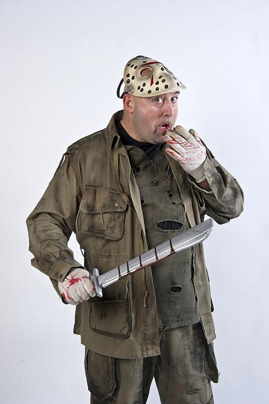 max pieriboni travestito da assassino da film horror, indossa una magliettta nera strappata e una giacca marrone sporca, un paio di guanti bianchi sporchi di sangue e una maschera leggermente rialzata per scoprire il viso, tiene in mano una spada sporca di sangue, su sfondo bianco