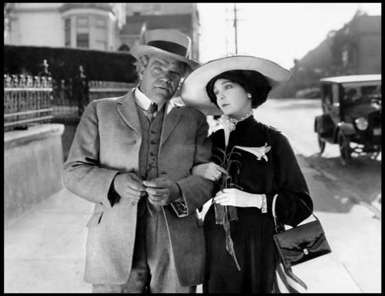 Greed, una scena del film in bianco e nero, con un signore e una sgnora a braccetto, vestitoìi in abiti del 1920