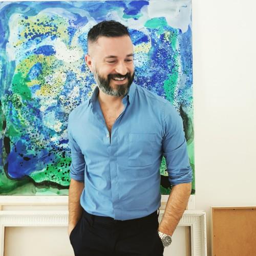 Massimo Ferragina con camicia azzurra e pantaloni scuri ha le mani in tasca e sorride