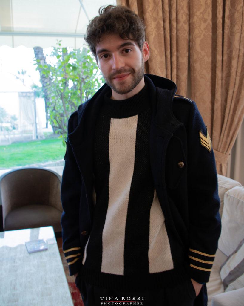 Matteo Faustini con giubbotto scuro, manu i in tasca, barba incolta e capello corto, in un salotto dell'hotel