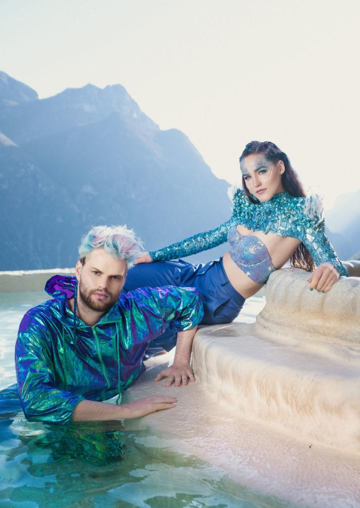 Il duo Sofi Tukker, entrambi gli artisti indossano dei costumi blu lucenti, lui è in acqua mentre appoggia le braccia su un gradino, indossa una giacca impermeabile blu lucente, lei è sdraiata su un gradino più in alto ed è dietro di lui, indossa un reggiseno azzurro turchese, un coprispalle azzurro con brillantini e un paio di pantaloni larghi blu, dietro ci sono delle montagne