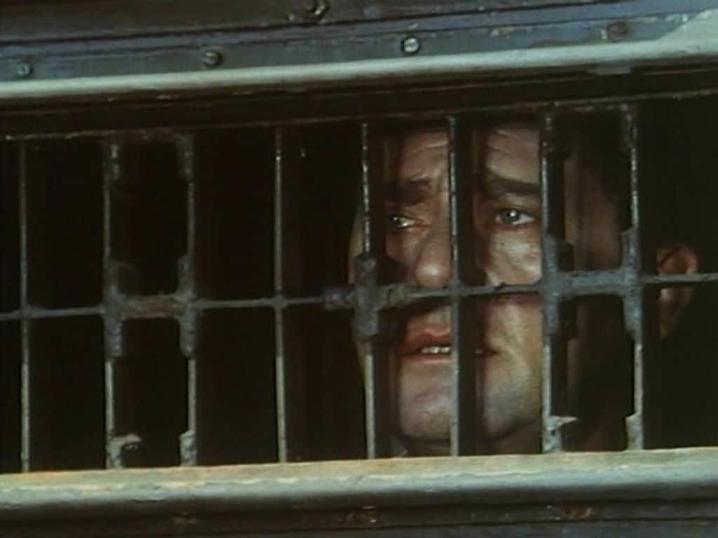 immagine da detenuto in attesa di giudizio, con l'attore romano ritratto deitro le sbarre di una cella