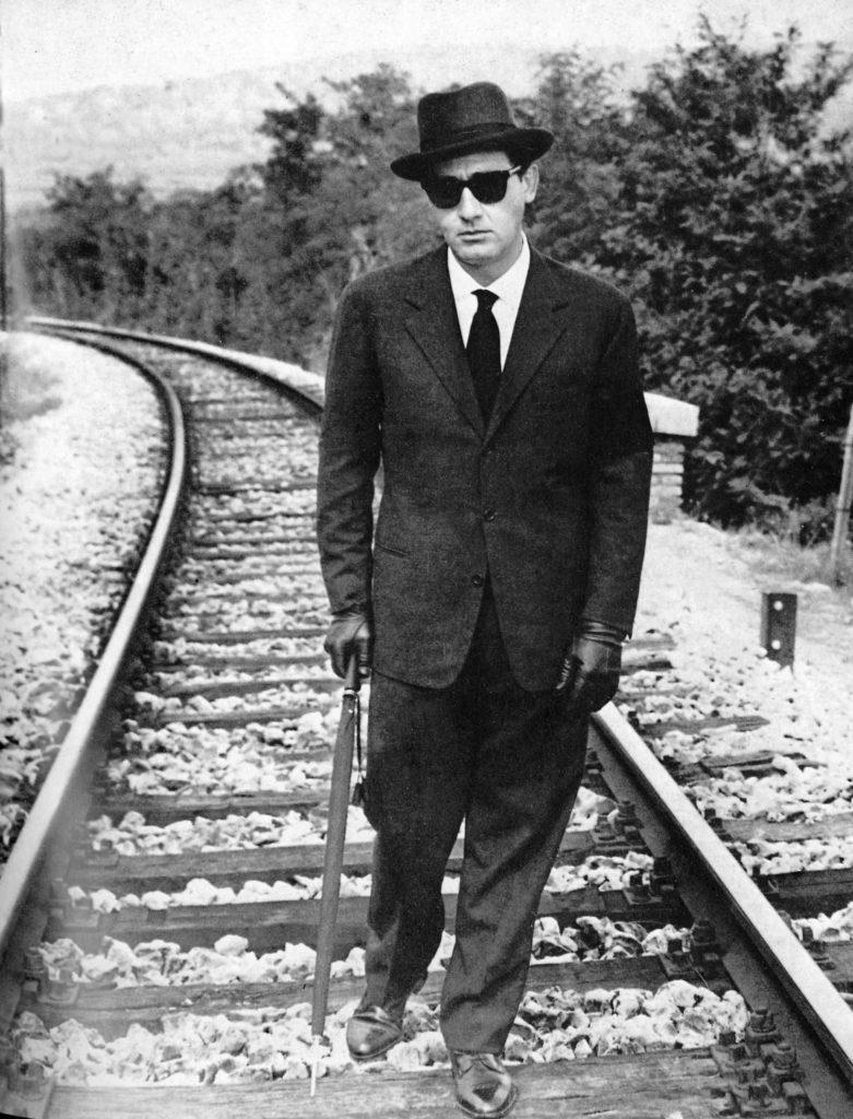 """inquadratura del film """"il vedovo2, che ritrae l'attore romano vestito di nero, con occhiali scuri e bastone"""