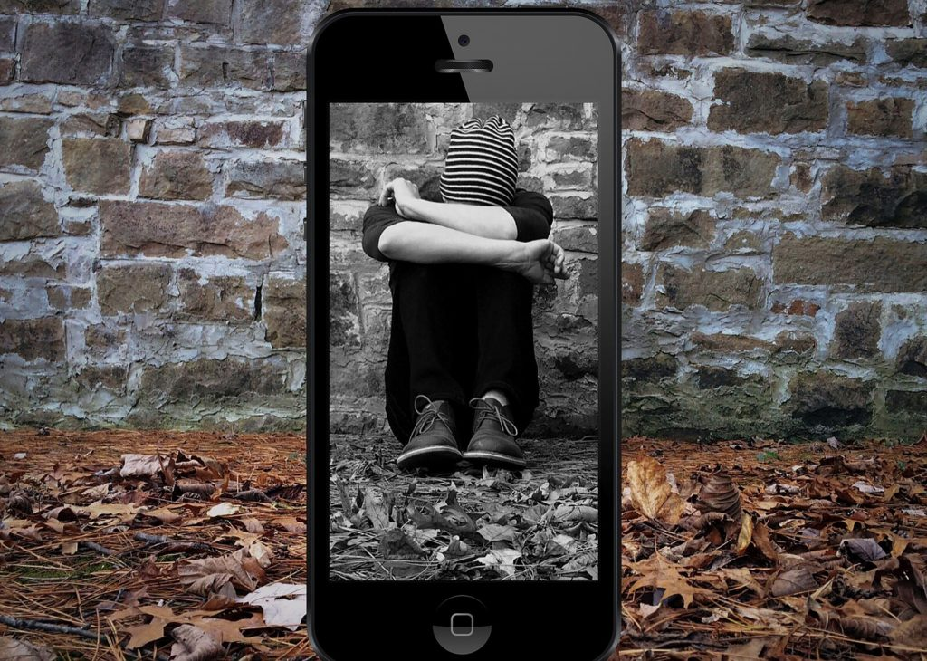 Un. Bambino dernto il telfono accovacciato e piangente simbolo del 7 febbraio contro cyberbullismo e