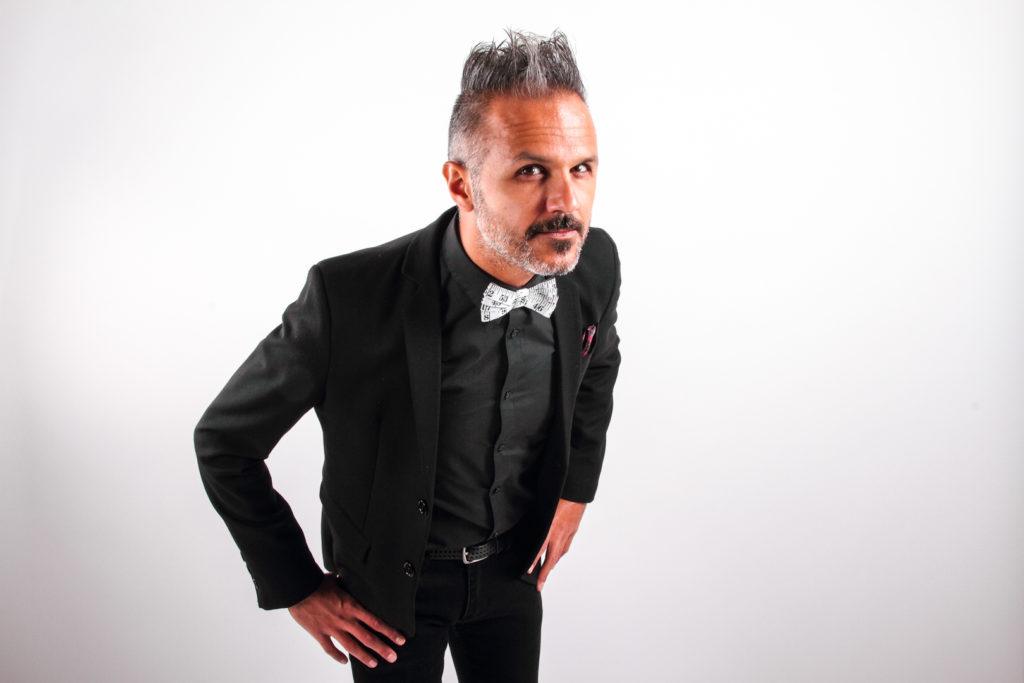 Paolo Franceschini su sfondo bianco, leggermente chinato in avanti, con sguardo serio, appoggia le mani al bacino, indossa un completo elegante nero, con un papillon bianco