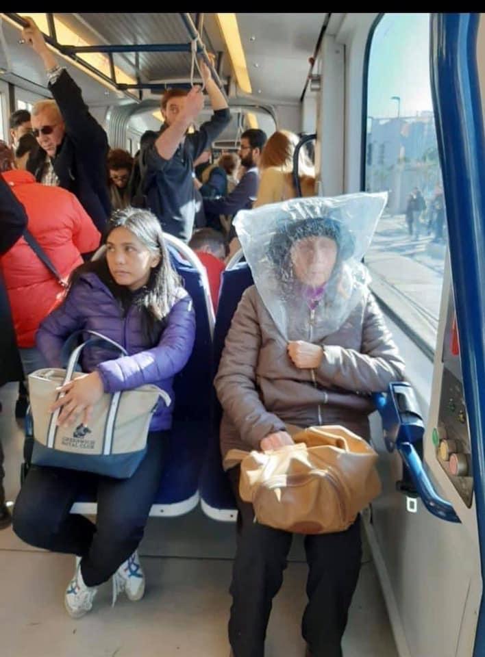 un'anziana seduta su un bus con un sacchetto di plastica in testa per proteggersi dal contagio