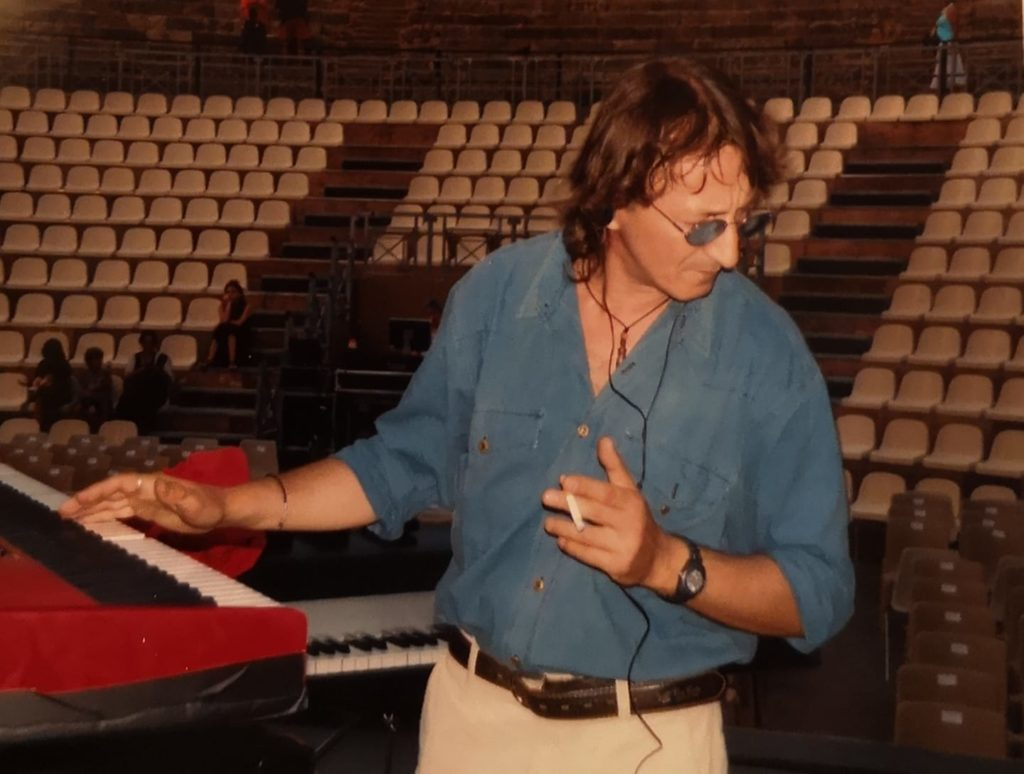Addio a Joe amoruso, tastirista di Pino daniele: prmo piano del musicista con una mano appoggiata alla tastiera, che indossa una camicia di jeans