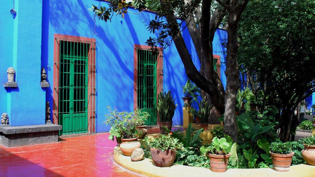 Il. Cortile di casa Azul porte verdi e pareti blu con. Piante davnti Frida apre Casa Azul, faces of Frida per #iorestoacasa