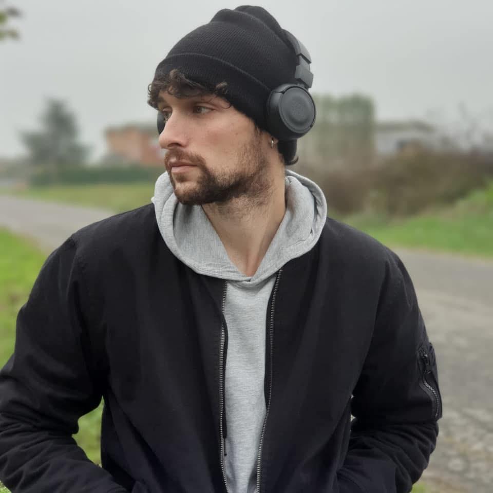"""Zoizi pubblica il nuovo singolo """"Odore"""": primo piano che lo ritrae con adddossso un giubbotto nero, una felpa grigia, un berretto di lana nero e le cuffie stereo in testa"""