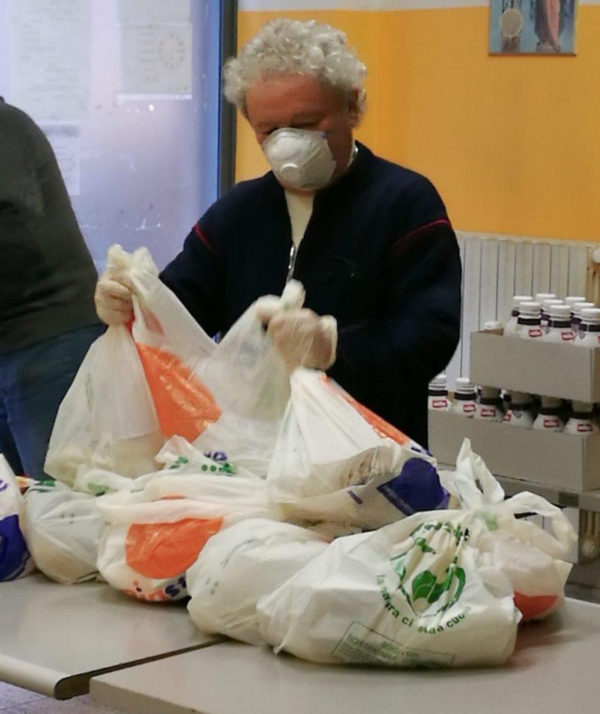 #lacaritànonsiferma mensa dei poveri don Adriano con mascherina sul viso prepara i pacchetti pasto per i poveri
