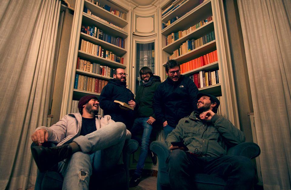 """Under The Bed, fuori il nuovo EP """"Controlled Filth"""" la foto ritrae i 5 membri della band con alle spalle una libreria"""