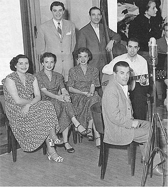 Nella foto in bianco e nero da sinistra seduta Nilla Pizzi, il Duo Fasano, un musicista dell'orchestra e in piedi alle loro spalle Achille Togliani. Davanti agli interpreti un microfono per le prove