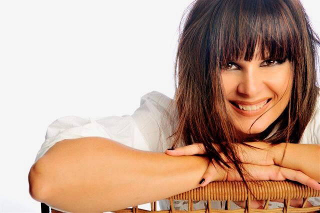 """""""Messaggio D'amore"""": POP Officine Popolari con la partecipazione di Silvia Mezzanotte. Primo piano della cantante bolognese, sorridente, appoggiata alla spalliera di una sedia di legno"""