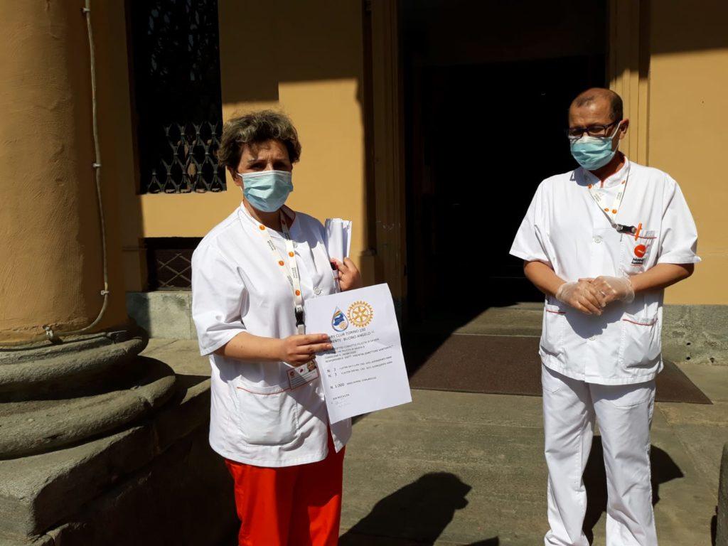 Rotary e covid-19 emergenza coronavirus due persone del personale sanitario di una struttura hanno in mano un cartone di mascherine e dei flaconi di disinfettanti davanti alla porta di una struttura ospedaliera