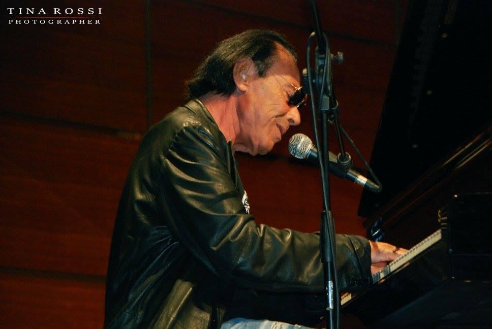Antonello Venditti, nella notte di roma. Nella foto il cantante seduto al pianoforte, intento a suonare, che indossa una giacca di pelle nera