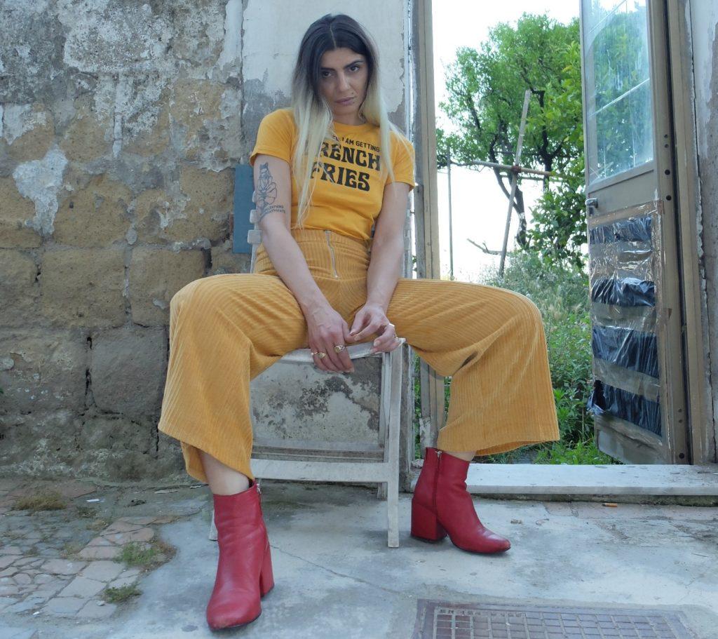 """Da Blonde fuori il primo disco solista """"Parlo ai cani"""". Nella foto la cantante napoletana, seduta su una sedia che indossa pantaloni e maglietta gialli, stiveletti rossi"""