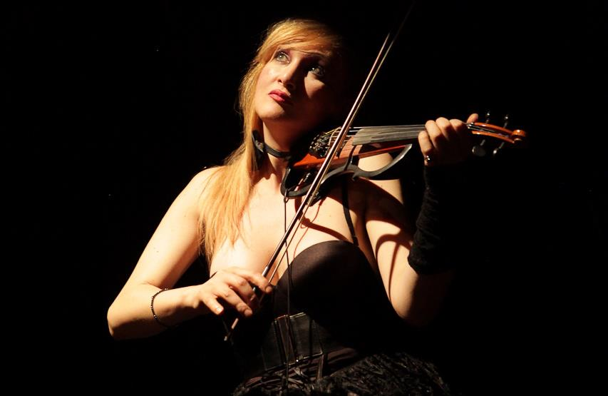 """H.E.R. """"Il mondo non cambia mai"""". Nella foto la violinista, bionda, che indossa un abito nero e scollato, mentre è intenta a suonare il violino."""