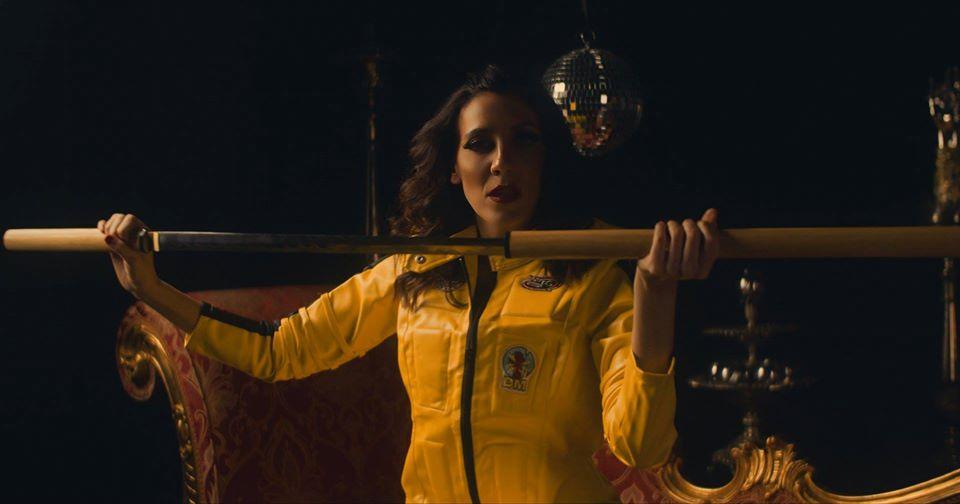 Marquica persenta il singolo catarifrangenti. nella foto la cantante, che indossa una tuta gialla, intenta a sfoderare una katana