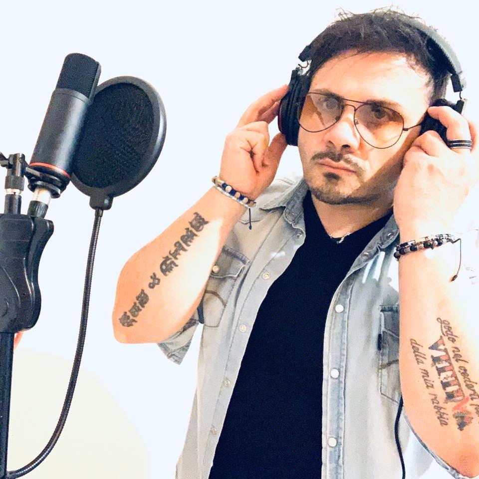 certe promesse, il nuovo singolo di mauro tummolo. nella foto il cantautore lucano, davanti a un miscofono, che indossa occhiali da sole, canotta nera e camicia grigia a maniche corte