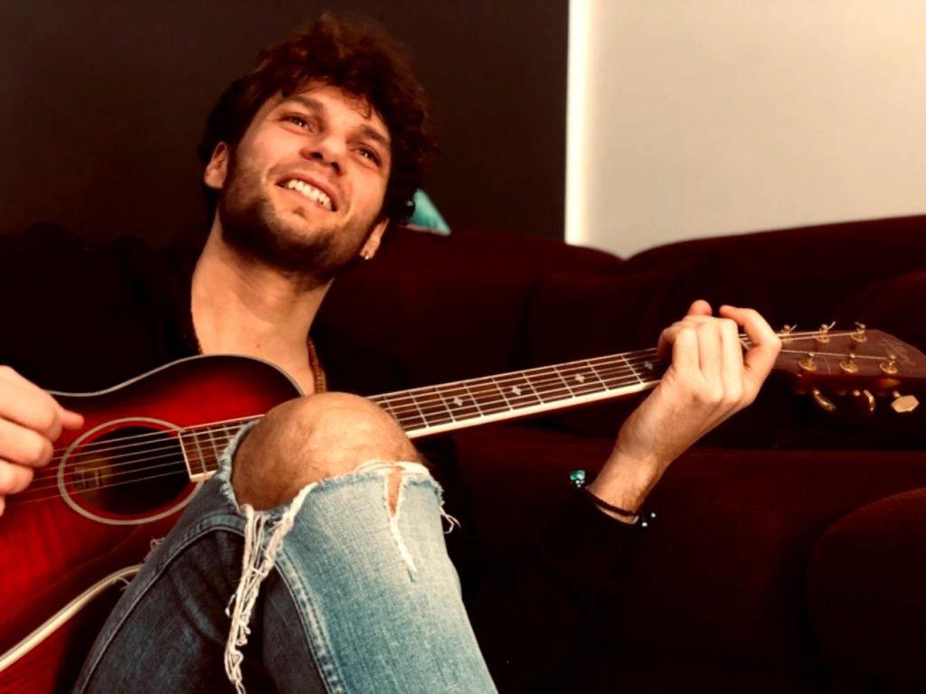 """Napo un milione di visualizzazioni per """"Supereroe"""". Nella foto il cantante, seduto e con la chitarra acustica in mano, che indossa jeans strappati, e una camicia nera. Sorride all'obiettivo."""