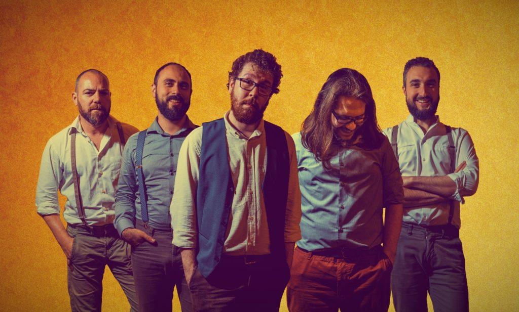 """""""Yet to Be Done"""" il nuovo singolo di Nasby & Crosh. Nella foto i 5 membri della band milanese, ritratti su uno sfondo giallo"""