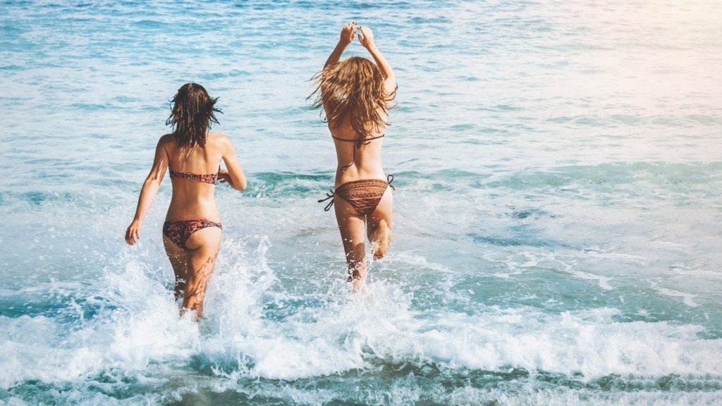bonus vacanze albergatori nella foto due ragazze in bikini entrano in mare