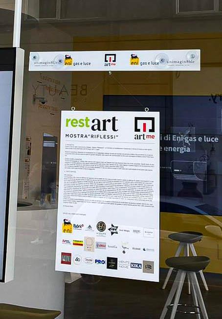 La locandina di Restart la mostra di ArtMe esposta sulla vetrina di un negozio eni store