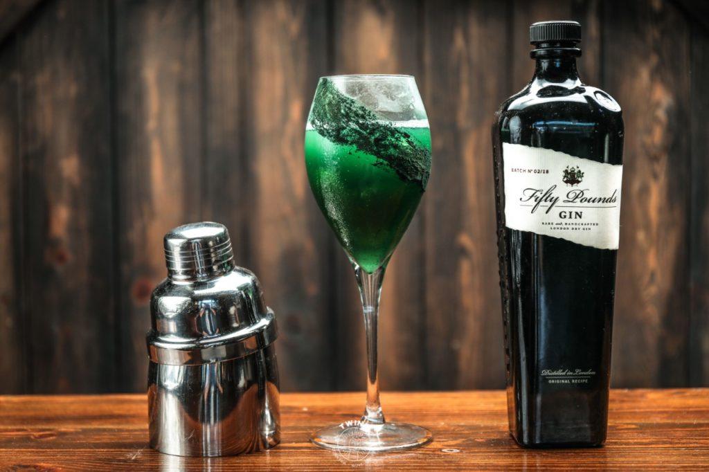 drink verde in bicchiere con vicino una bottiglia e il tappo di uno shaker