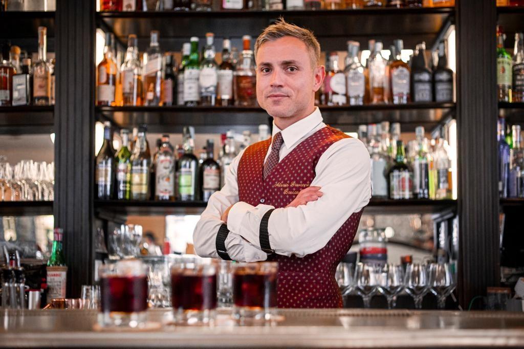 Can be sweet nella foto Alessio Giovannesi bartender con gille granata e camicia bianca dietro il bancone del bar con tanti bicchieri davanti