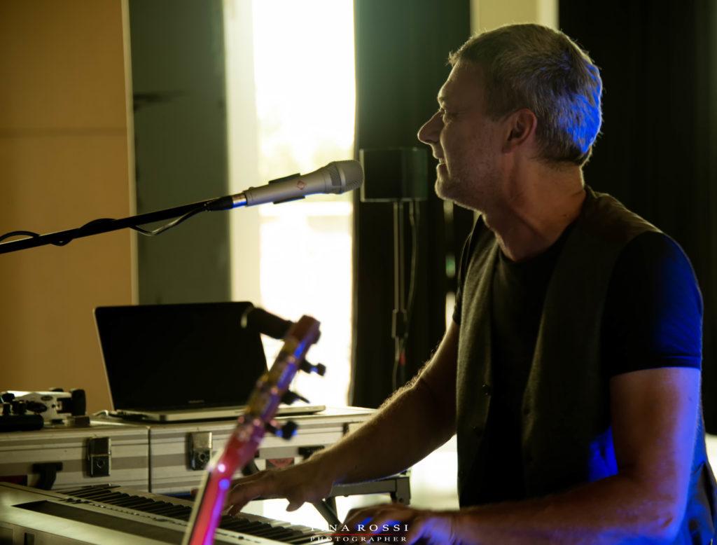 Alex D'Herin live nella foto Alex sta suonando una tastiera e canta