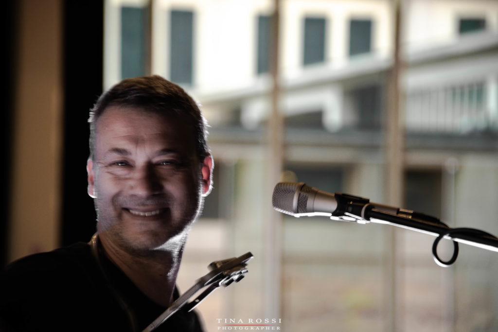 Alex D'Herin in un primo piano sorridente con un mixrofono sulla destra