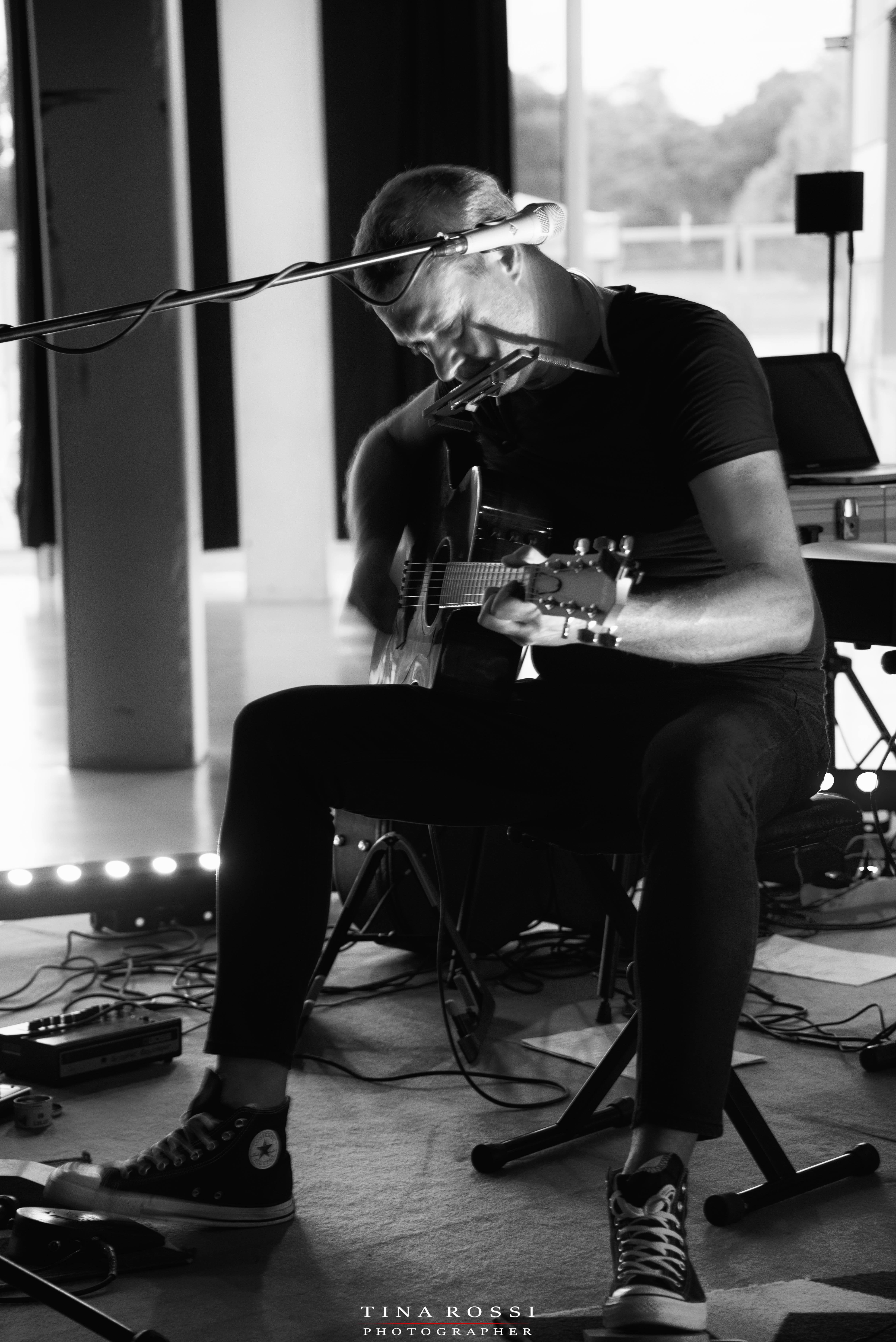 Alex D'Herin live nella foto in bianco e nero seduto davanti a un microfono con chitarra in mano