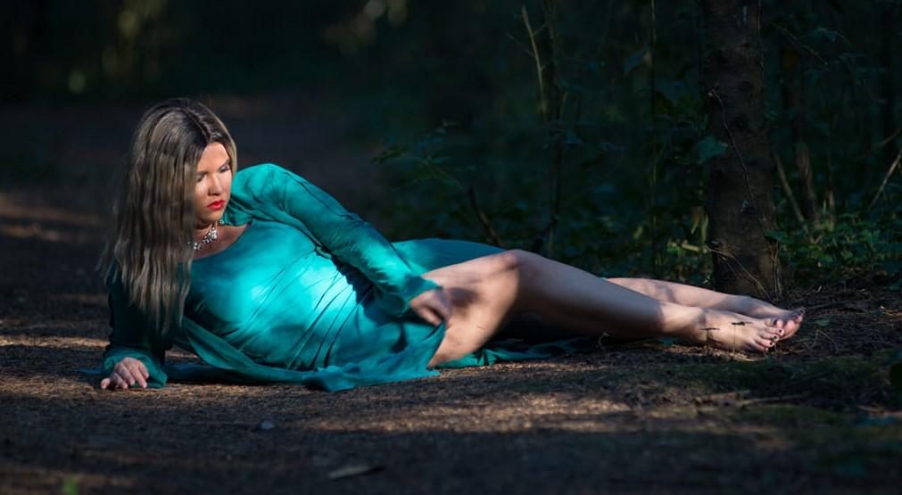 """Francesca Laurie Aureli """"Time and again"""". Nella foto Laurie sdraiata all'interno di un bosco, che indossa un vestito azzurro, che lascia scoperte le gambe"""
