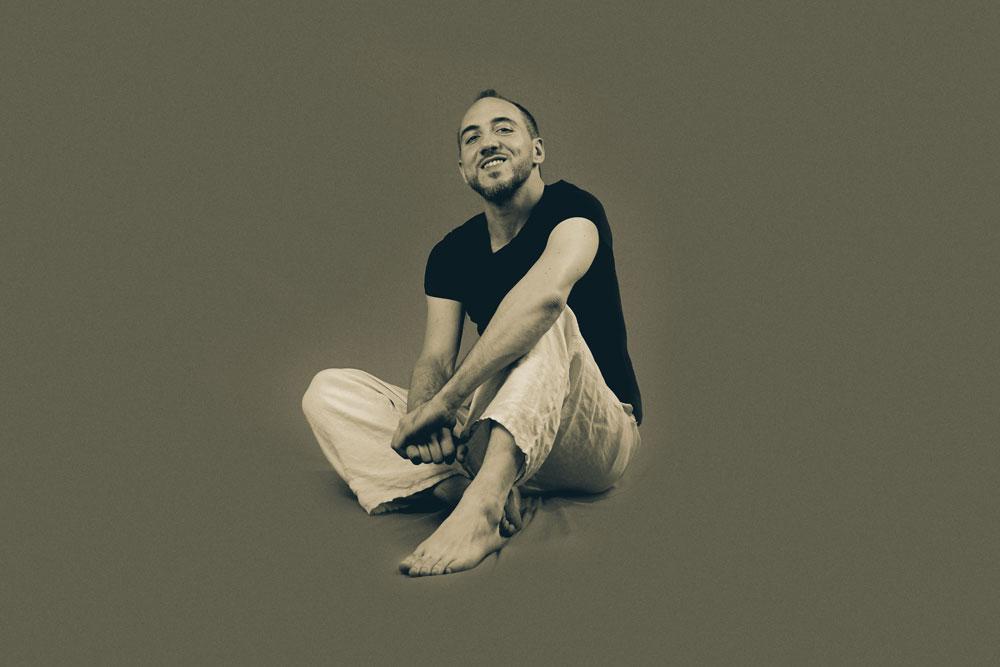 gerolamo sacco la prima estate del mondo. nella fotosu sfonfo grigio è inquadrato l'artista, pantaloni bianchi e t-shirt nera, seduto con le gambe incrociate