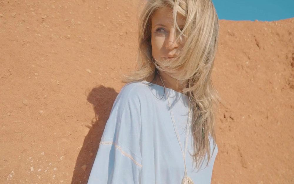"""Haiducii """"Respira"""". nella foto la cantante rumena, i lunghi capelli biondi sciolti, girata di profilo, davanti a una duna di sabbi, che indossa una tunica bianca"""