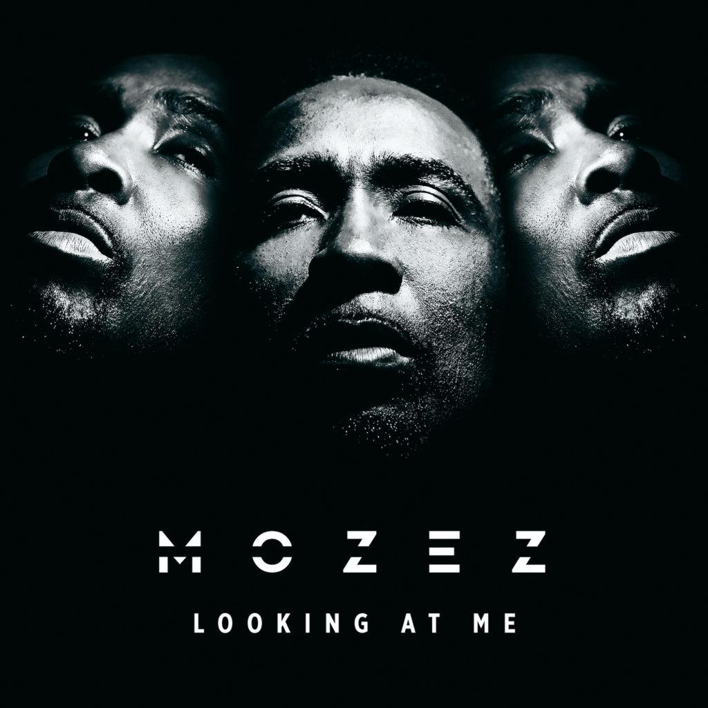 """Mozez """"Looking at me"""". La foto in ianco e nero ritrae l'artista giamaicano, in tre facce disposte a triangolo, con la scritta bianca del titolo sotto l'inquadratura"""