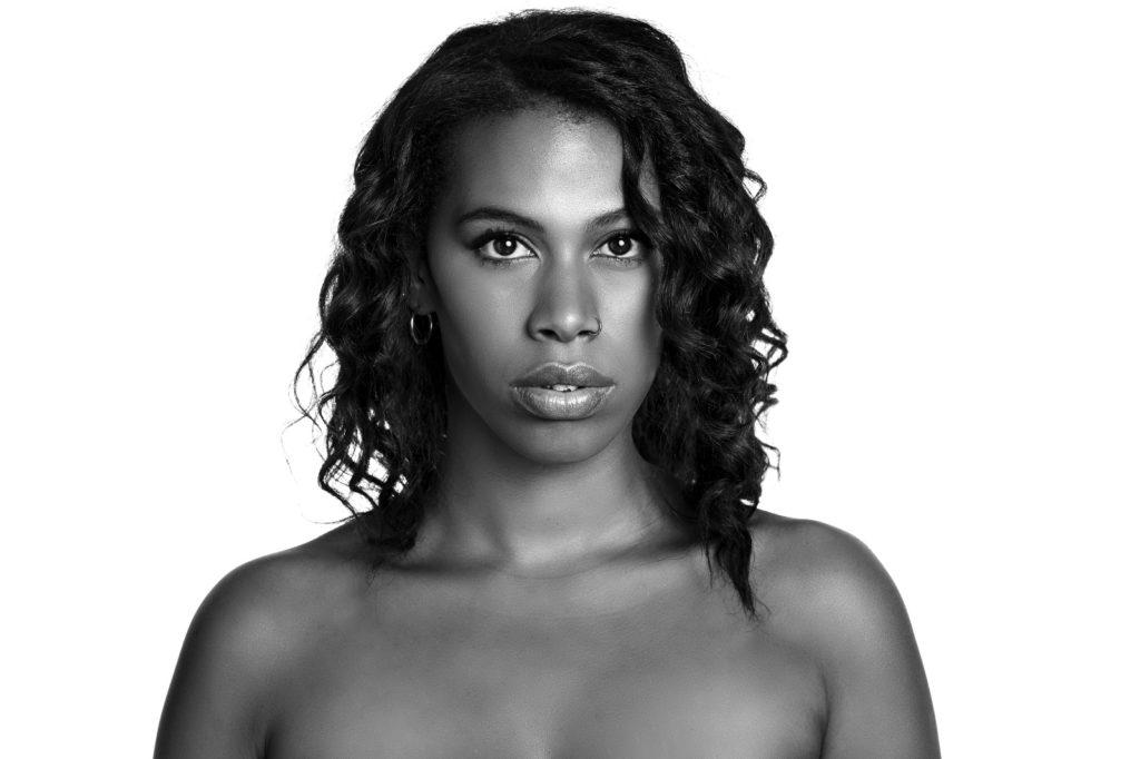 """""""Disarmata"""" il singolo per l'estate di Sherol Dos Santos. Foto in bianco e nero, primo piano, della giovane cantante, spalle nude e lunghi capelli ricci e sciolti"""