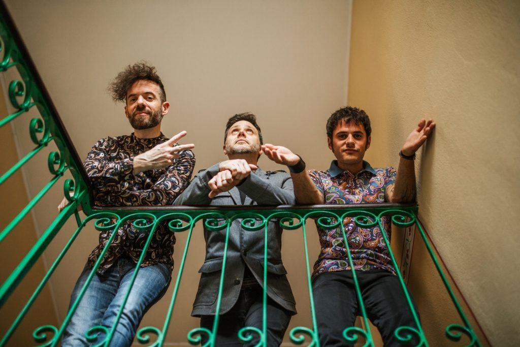 """The Monkey Weathers  """"matilda"""". Nella foto i tre ragazzi della band, che indossano camicie a fiori, appoggiati a una ringhiera, su un pianerottolo"""