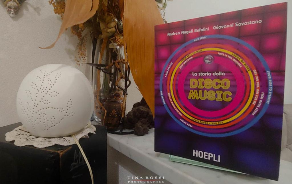 la storia della disco music il libro appoggiato in piedi vicino ad un vaso di fiori e a una palla illuminata