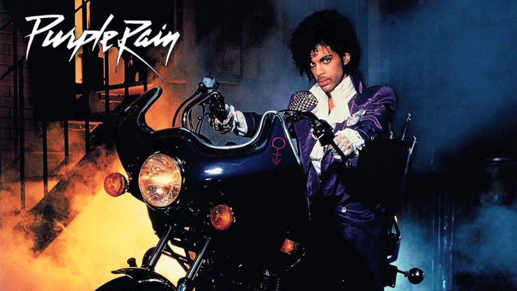 purple rain prince. la copertina del disco, che ritrae il cantante americano, giacca viola e camicia bianca, in sella a una moto nera