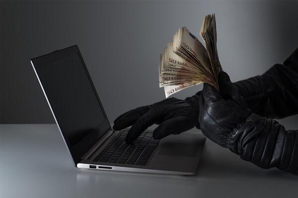 truffe per artisti un pc in ombra con una mano guantata di nero con tanti soldi