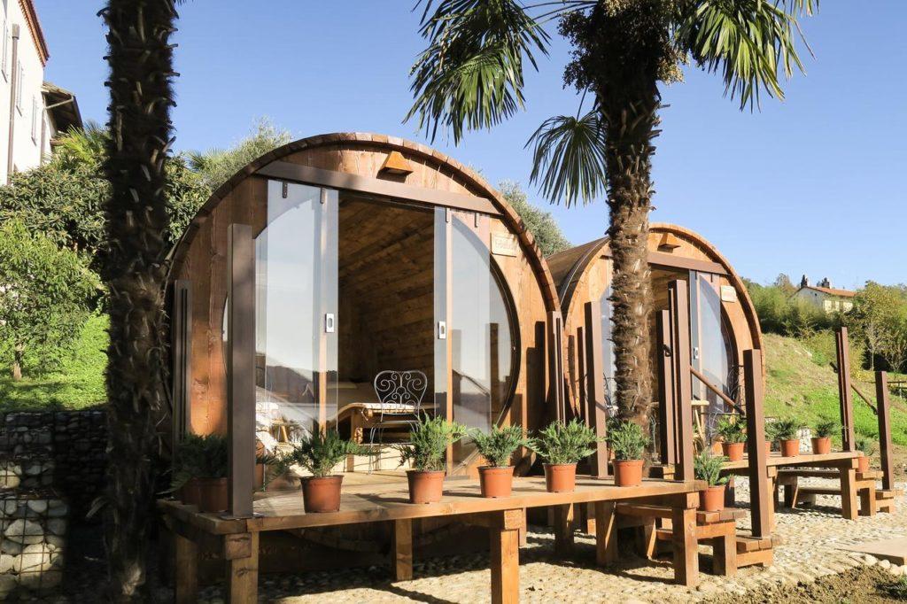 Delle stanze all'aperto a forma di botti giganti e dei tavoli di legno