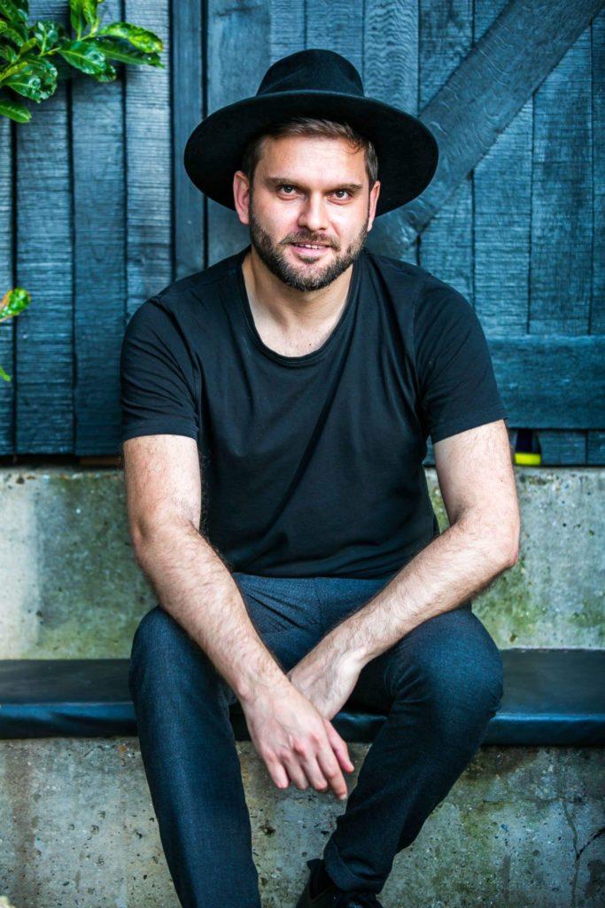 danilo sapienza - un momento - il cantante siciliano, seduto, con indossso maglietta nera, jeans e cappello a tesa larga di colore nero